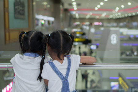 Two cute asian child girls waiting for boarding in the airport together Stock Photo