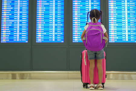 Cute asian child girl with backpack checking her flight at information board in international airport terminal