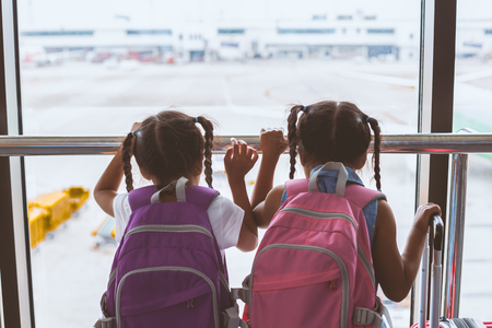 Two cute asian child girls with backpack looking at plane and waiting for boarding in the airport together