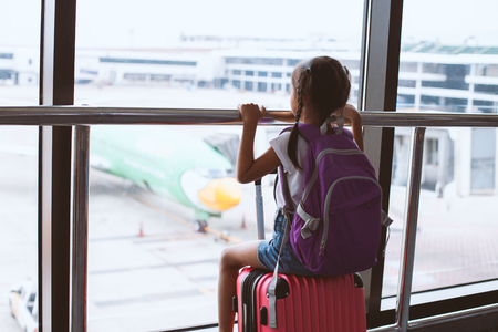 Cute asian child girl with backpack looking at plane and waiting for boarding in the airport