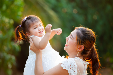 Asian mother carrying her daughter up in the air and playing together in the park with fun and love Banco de Imagens