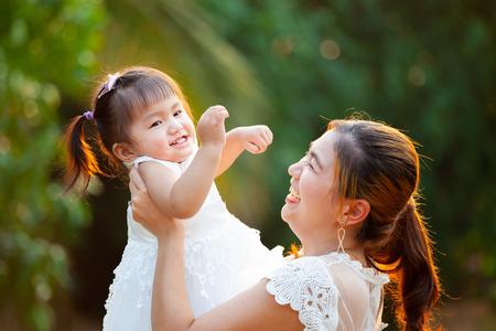 Madre asiatica che porta sua figlia in aria e gioca insieme nel parco con divertimento e amore Archivio Fotografico
