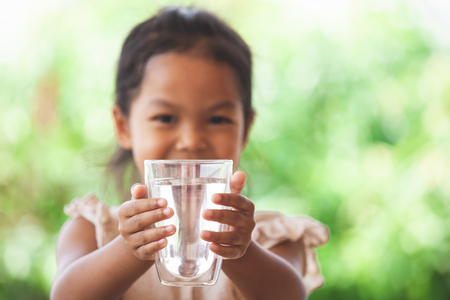 Cute asian child girl like to drink water and holding glass of fresh water in green nature background