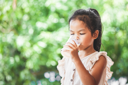 Cute asian child girl is drinking a milk from glass on green nature background Imagens