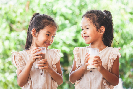 Two cute asian child girls drinking a milk from glass together on green nature background Stockfoto