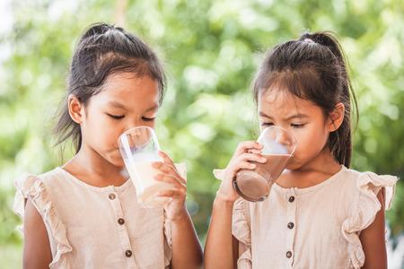 Twee schattige Aziatische kindmeisjes die samen melk uit glas drinken op groene natuurachtergrond