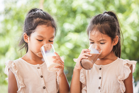 Two cute asian child girls drinking a milk from glass together on green nature background