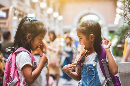 Two cute asian child girls with backpack eating pancake together after school in the school Stockfoto