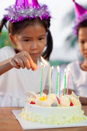 Cute asian child girl lighting candle on birthday cake in birthday party Stockfoto