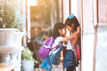 Back to school. Two cute asian child girls with school bag playing together after school in the school