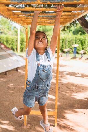 Cute asian child girl hang the bar by her hand to exercise in the playground with fun and strong