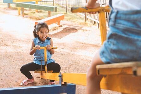 Zwei süße asiatische Kindermädchen, die zusammen auf dem Spielplatz mit Spaß Wippe spielen