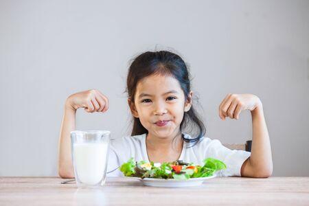 Niña asiática linda que come verduras saludables y leche para su comida