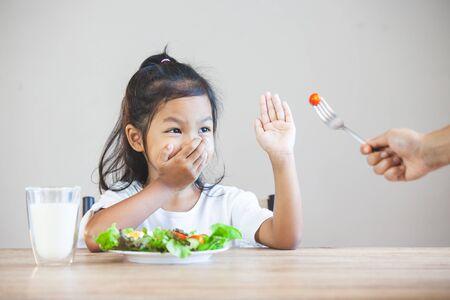 아시아 어린이는 야채를 먹는 것을 좋아하지 않고 건강한 야채를 먹는 것을 거부합니다 스톡 콘텐츠
