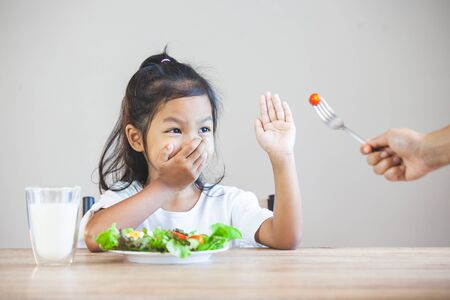 Asian child does not like to eat vegetables and refuse to eat healthy vegetables Banco de Imagens