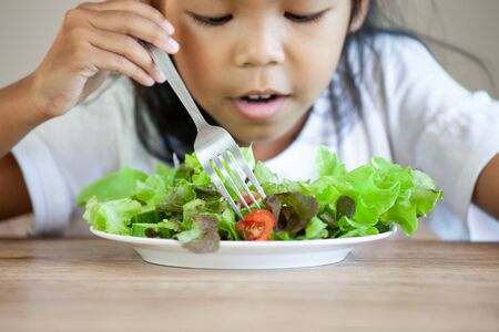 Cute asian child girl eating healthy vegetables for her meal Reklamní fotografie