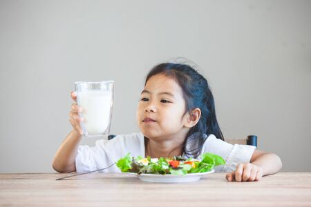 Cute asian child girl eating healthy vegetables and milk for her meal