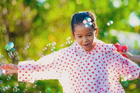 Cute asian child girl wearing raincoat having fun to play with bubbles in outdoor after rainy