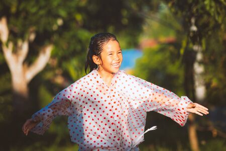 Happy asian child girl wearing raincoat having fun to play with the rain in the sunlight