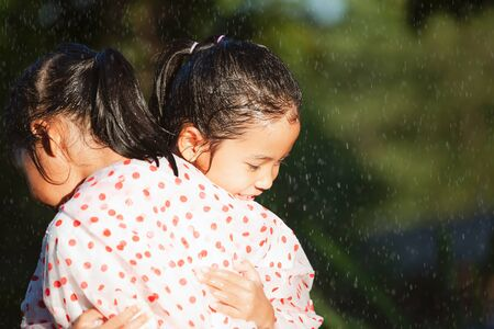 Two asian child girls wearing raincoat hugging each other with love in the rainy day