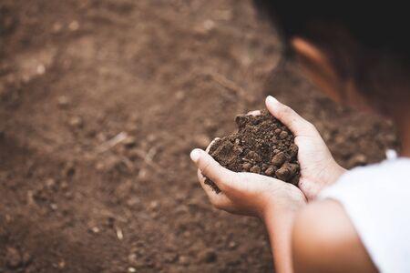 Kinderhand, die den Boden in Herzform hält, bereiten sich darauf vor, den Baum zu pflanzen