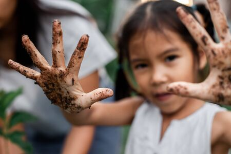 Asian child girl showing dirty hands after planting the tree in the garden Reklamní fotografie