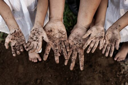 Family parent and children showing dirty hands after planting the tree together in the garden