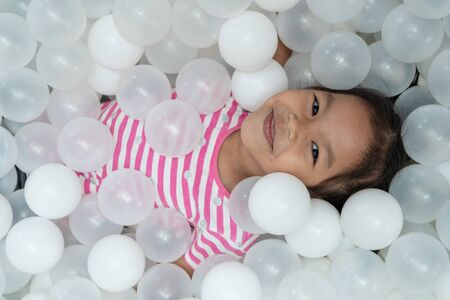 Happy cute asian child girl having fun to play with white plastic balls in the playground