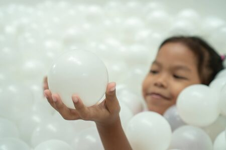 Cute asian child girl holding the ball and having fun to play with white plastic balls in the playground