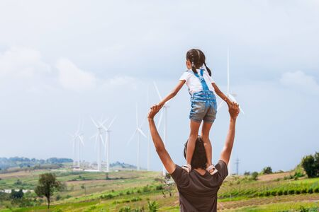 Father and daughter having fun to play together. Asian child girl riding on fathers shoulders in the wind turbine field