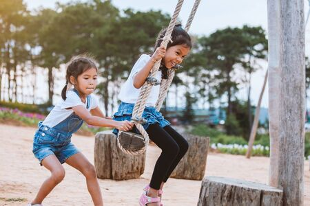 Happy asian child girl having fun to play on wooden swings with her sister in playground with beautiful nature Reklamní fotografie