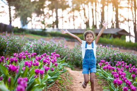 Cute asian child girl raise their arms and run in the flower garden with freshness and happiness