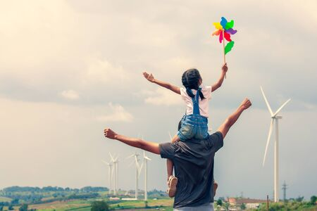 Father and daughter having fun to play together. Asian child girl playing with wind turbine and riding on fathers shoulders in the wind turbine field