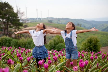 Two asian child girls raise their arms in the flower garden together with freshness and happiness