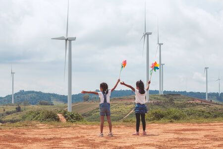 Two asian child girls playing with wind turbine toy and looking at wind turbine field together with freshness