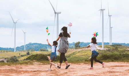 Two asian child girls and their mother are running and playing with wind turbine toy together with fun in the wind turbine field Reklamní fotografie