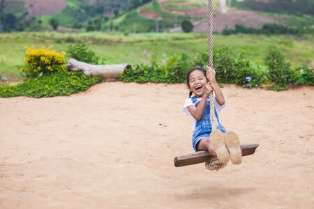 Happy asian child girl having fun to play on wooden swings in playground with beautiful nature