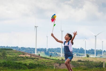 Cute asian child girl is running and playing with wind turbine toy  with fun in the wind turbine field