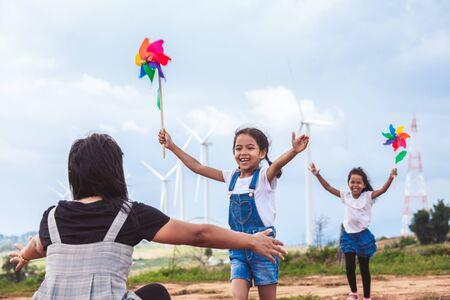 Two asian child girls playing with wind turbine toy and running to their mother to give a hug in the wind turbine field Reklamní fotografie