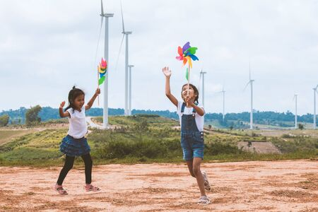 Two asian child girls are running and playing with wind turbine toy together with fun at wind turbine field Reklamní fotografie