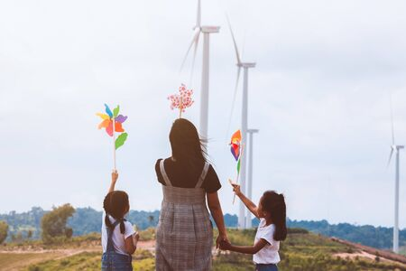 Two asian child girls and their mother playing with wind turbine toy together with fun in the wind turbine field