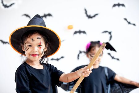Two cute asian child girls wearing halloween costumes and makeup having fun on Halloween celebration together 版權商用圖片