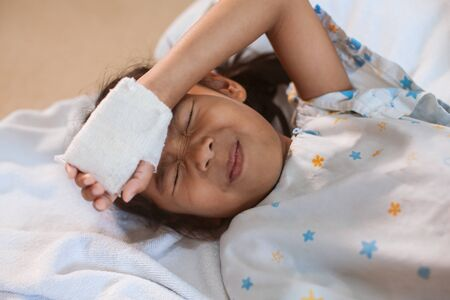 Sick asian child girl who have IV solution bandaged suffering from headache and feeling unwell in the hospital
