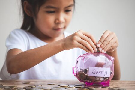 Cute asian child girl putting money into piggy bank to save money for the future