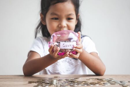 Cute asian child girl holding piggy bank and putting money into piggy bank to save money for the future