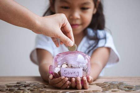 Cute asian child girl holding piggy bank and parent putting money into piggy bank to save money for the future together