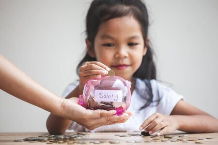 Parent hand holding piggy bank and Cute asian child girl putting money into piggy bank to save money for the future together