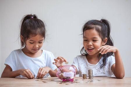 Two cute asian child girls putting money into piggy bank to save money for the future together with fun and happiness