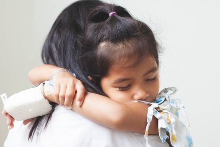 Sick asian child girl who have IV solution bandaged hugging her mother with love in the hospital Archivio Fotografico