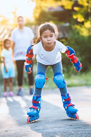Cute asian child girl riding on roller skates in the park with fun Foto de archivo - 131339126